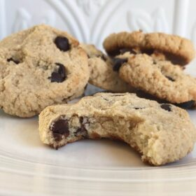 A pile of vegan tahini chocolate chip cookies with a bite missing from one.