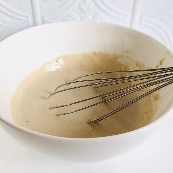 A bowl of creamy looking sauce with a whisk in it.