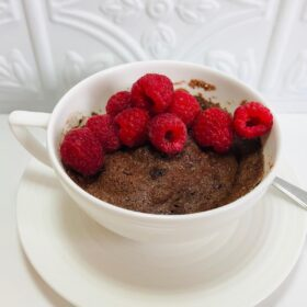 Cake in a mug with raspberries on top.