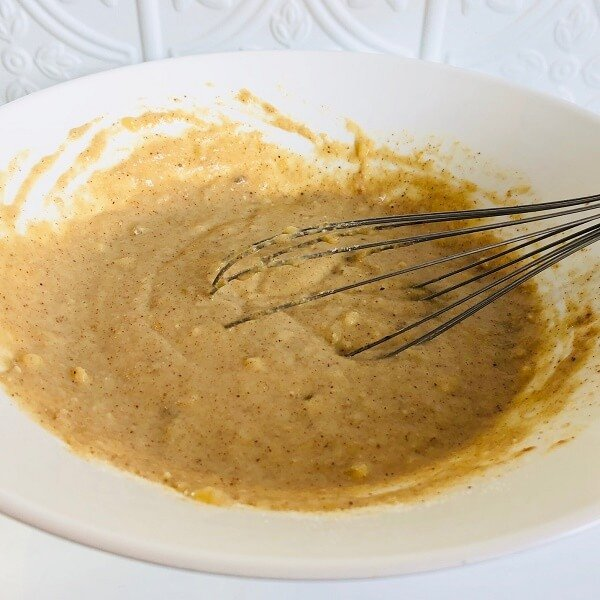 Pancake batter in a large bowl with a whisk.