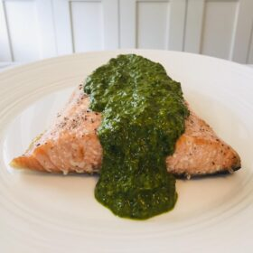 A piece of fish smothered in a green sauce.