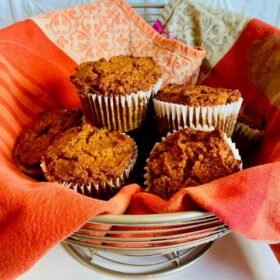 A wire basket of muffins wrapped in an orange tea towel.