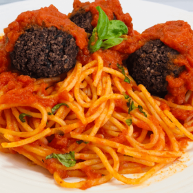 Pinterest image of plant based meatballs with pasta in a red sauce.