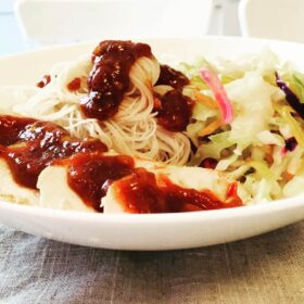 A bowl of noodles, chicken, and cabbage smothered in a red chili sauce.