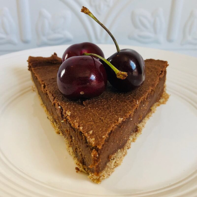 A slice of cheesecake with three cherries on top.