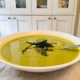 A bowl of green soup garnished with asparagus tips.