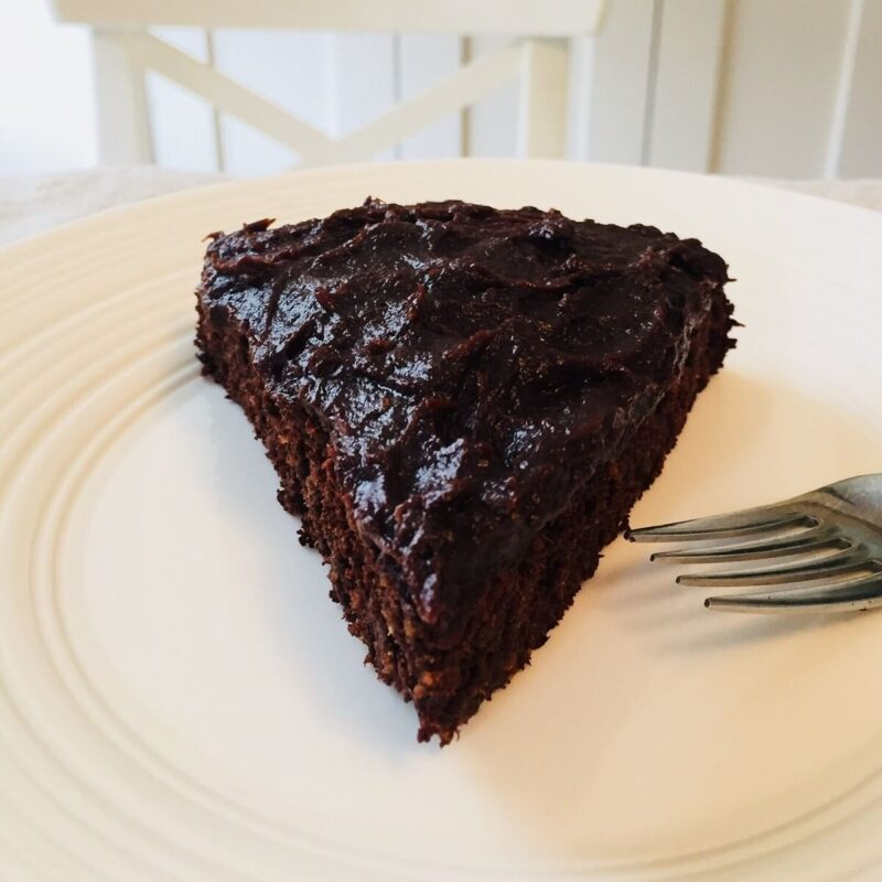 A large slice of chocolate cake on a white plate with a stainless steel fork.