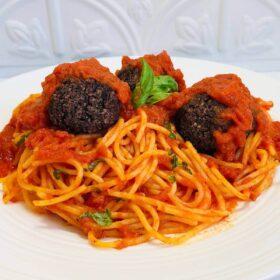 Three vegan meatballs on a plate of spaghetti with tomato sauce.