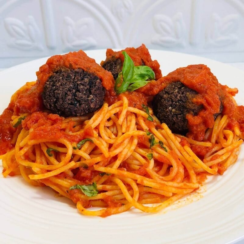Three vegan meatballs on a plate of spaghetti with tomato sauce.