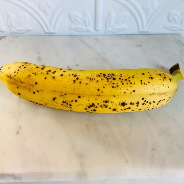 A ripe banana on a marble cutting board.