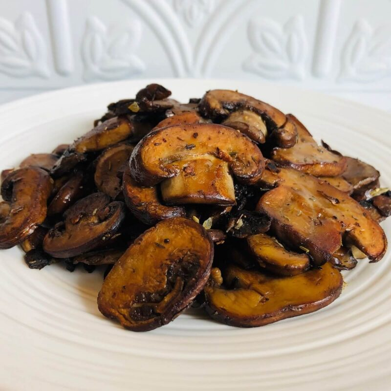 Sauteed mushrooms on a plate against a white tile background.