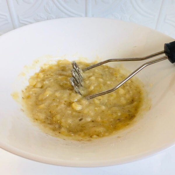 Mashed banana in a large white bowl.