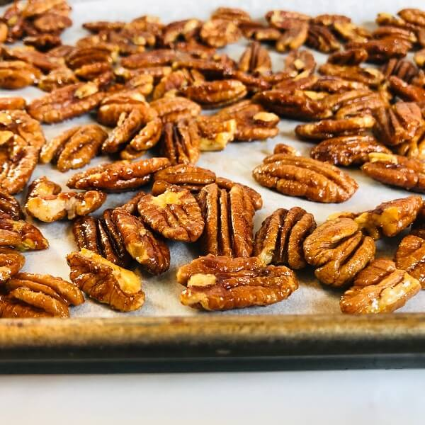 Pecans on a parchment paper lined sheet pan.