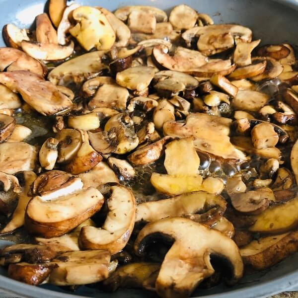 Mushrooms cooking in a frying pan.