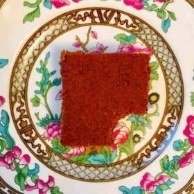 A piece of pumpkin cake on a colorful floral plate.
