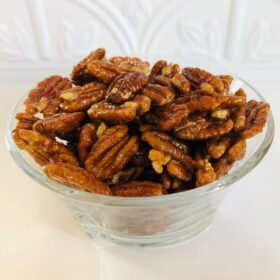 A glass dish filled with pecans.