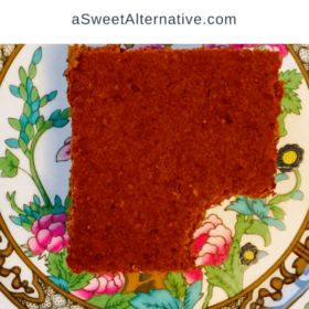 A square piece of pumpkin cake with a bite missing on a plate.