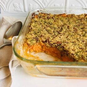 Sweet potato casserole in a glass dish with a scoop missing.