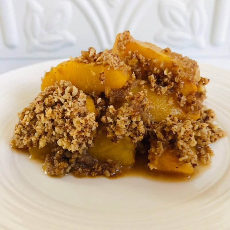 A serving of peach crisp on a white plate.