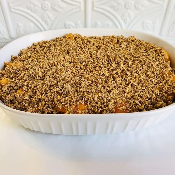 Raw peach crisp in a white casserole dish.