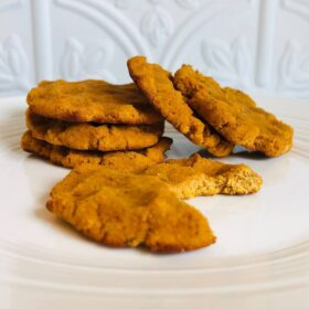Six pumpkin cookies displayed on a plate.