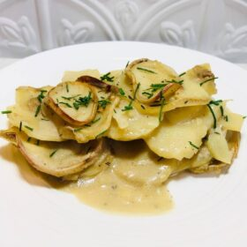 A white plate full of scalloped potatoes.