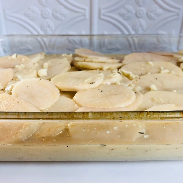 Raw sliced potatoes in a glass baking dish.