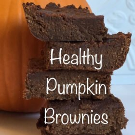 Brownies stacked on a white countertop in front of a pumpkin.