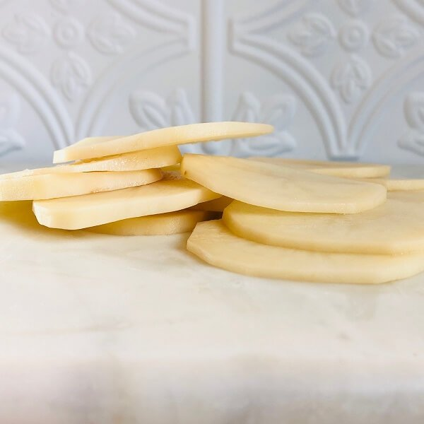 Thinly sliced potatoes on a marble cutting board.