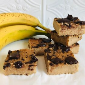 Some blondies stacked next to bananas.