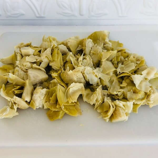 Chopped artichokes on a white cutting board.