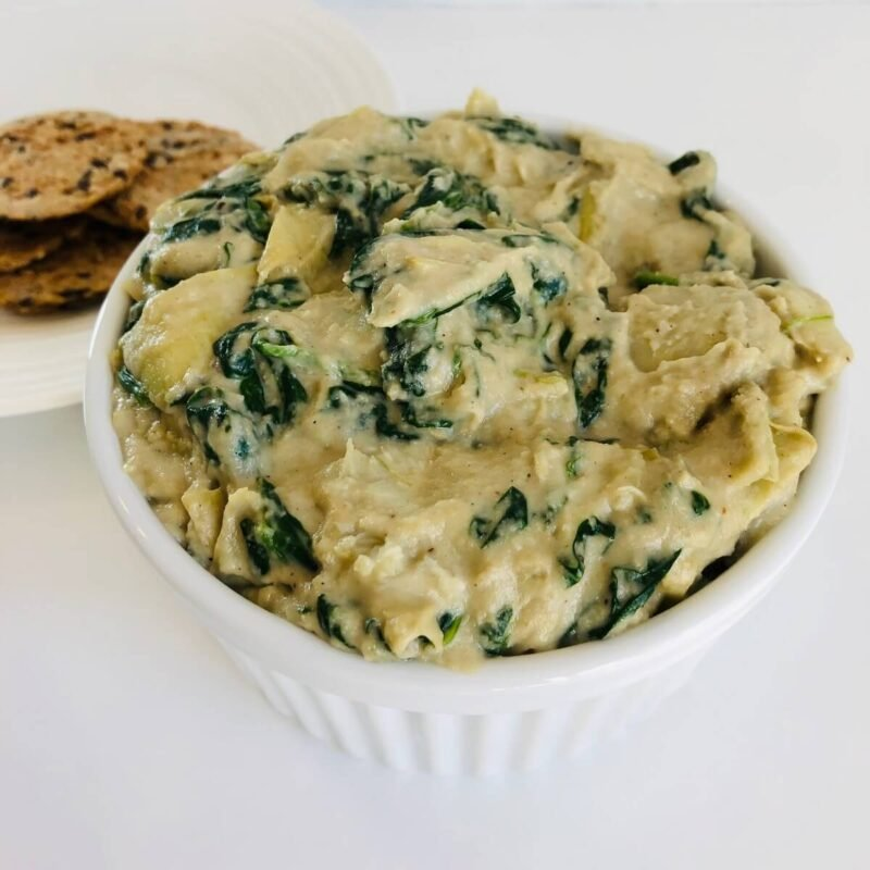 A bowl of spinach artichoke dip next to a plate of crackers.