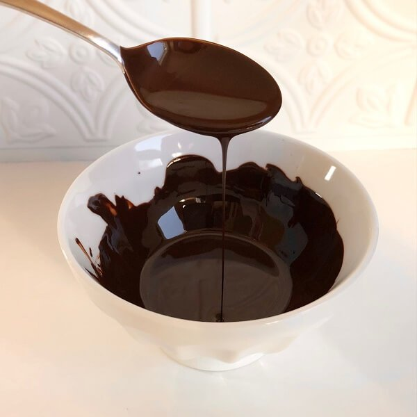 Melted chocolate dripping off a spoon.