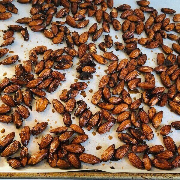 Candied almonds drying on a baking sheet.