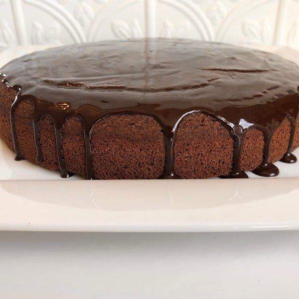A chocolate glazed cake on a white platter.