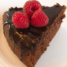 A slice of cake with chocolate glaze and raspberries on top.