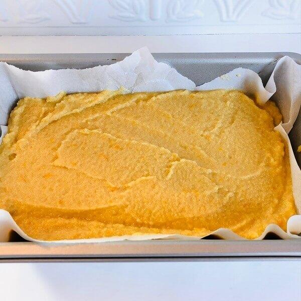 Raw orange cake batter in a loaf pan.