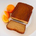 A loaf cake with a slice cut off next to oranges.