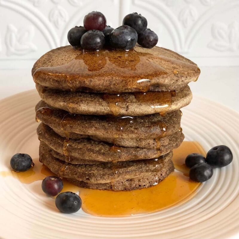 A stack of buckwheat pancakes dripping with maple syrup.