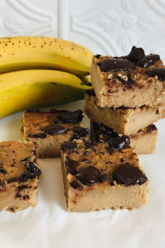 Blondies on a plate next to bananas.