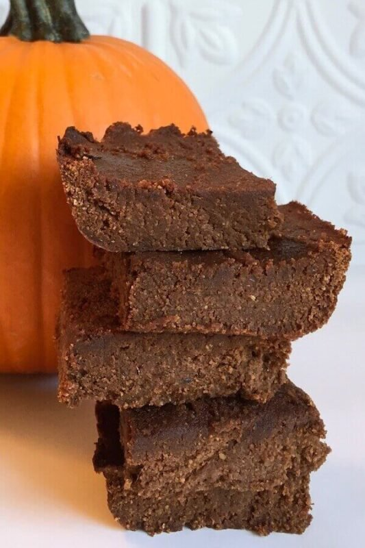 Brownies stacked next to a pumpkin.