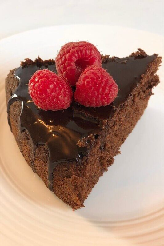 A slice of cake on a plate with raspberries on top.