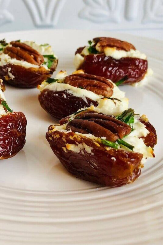 Stuffed dates arranged on a white plate.