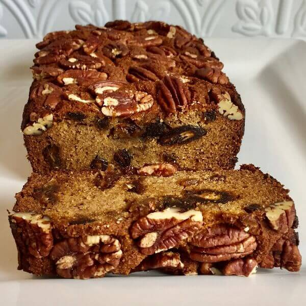 Fruitcake loaf with a slice cut off.