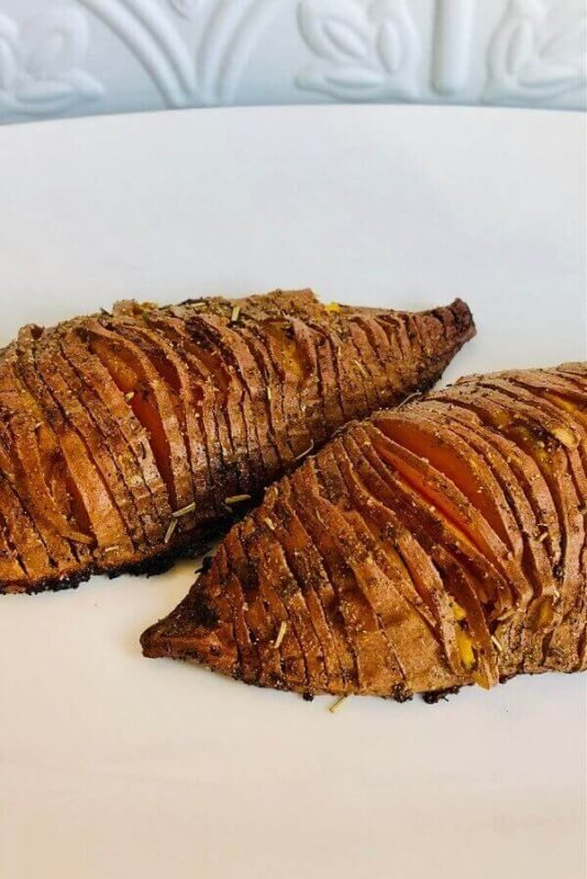 Hasselback potatoes on a white plate.