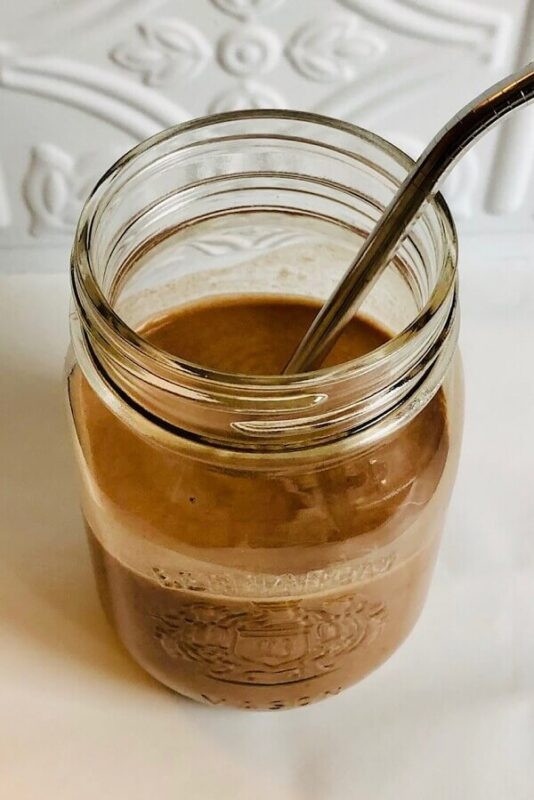 A chocolate smoothie in a glass jar.
