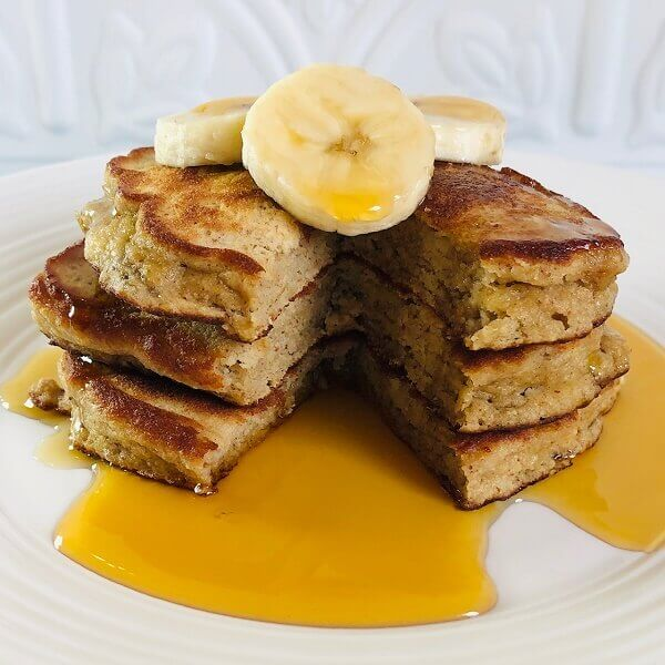 Pancakes with three banana slices on top.