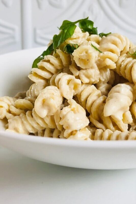 Pasta with tahini sauce in a white bowl.