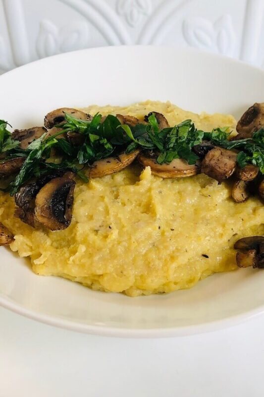 A bowl of polenta with mushrooms and herbs sprinkled on top.