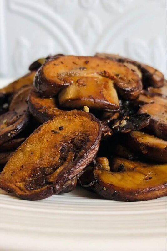 Sauteed mushrooms on a white plate.